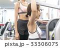 スポーツジムでウエイトトレーニングの説明を受ける若い女性 33306075