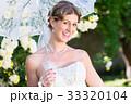 Bride at wedding with parasol in garden 33320104