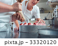 Confectioner or pastry chefs finishing cake with 33320120