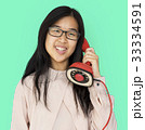Asian girl talking by phone studio portrait 33334591