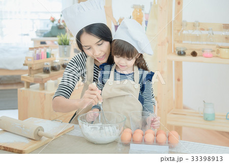 mother and her daughter make a cake in kitchenの写真素材 33398913