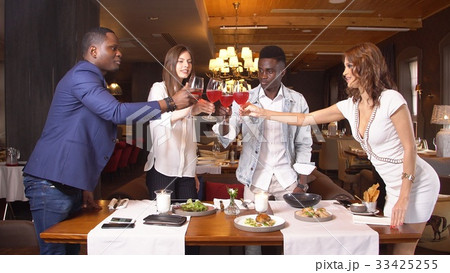 Group Of Young Friends Enjoying Meal In Restaurant 33425255