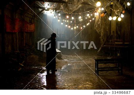 Man in black hat in the rain at dark overcast 33496687
