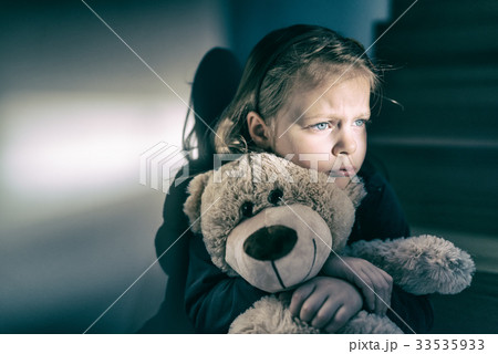 Sad little girl embracing her teddy bear - feels lonely 33535933