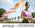 a thai woman is walking against flags while holding flower garland 33595058