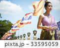 asian woman in traditional costume is standing next to flags and looking away 33595059