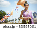 a photo of happy thai woman holding flower garland next to national flags 33595061