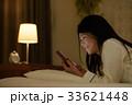 ベッドでスマホを見る女性 33621448