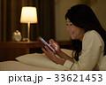ベッドでスマホを見る若い女性 33621453