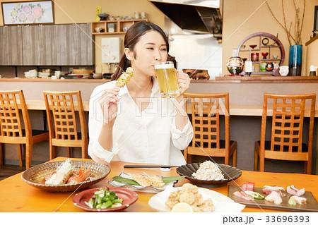 居酒屋で食事する女性 33696393