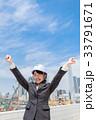 ヘルメットをかぶったスーツの女性が空に向かって両手を上げる 33791671