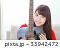 ギターを抱きかかえる若い女性 33942472