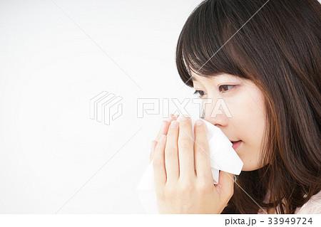 鼻をかむ若い女性 33949724