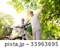 happy senior couple with bicycles at summer park 33963695