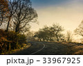 winding countryside road in late autumn fog 33967925