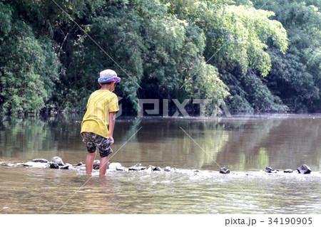 川で石拾いする少年 34190905