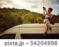 a girl is sitting on the top of a car and taking photos with her digital camera 34204998