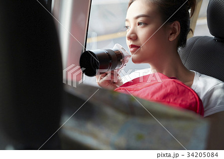a lovely girl is sitting in a car and holding digital camera 34205084