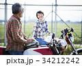 バイクに乗るシニアと女性 34212242