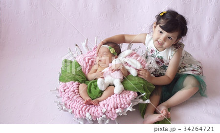 little girl looks at her baby sister. 34264721