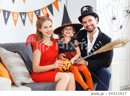 happy family in costumes getting ready for halloween at home 34321027