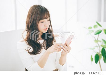 スマートフォンを操作する笑顔の女性   34325188