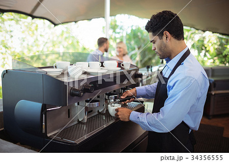 Waiter making cup of coffee from espresso machine 34356555
