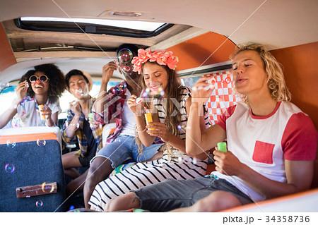 Happy friends blowing bubble wands in camper van 34358736