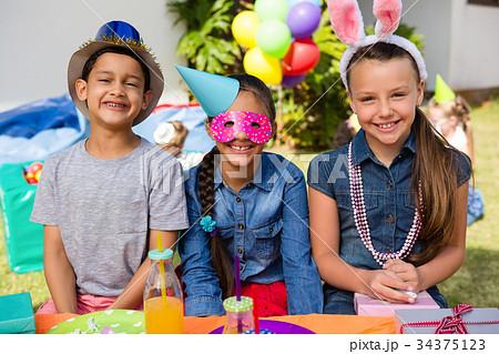 portrait of happy children sitting at tableの写真素材 34375123 pixta