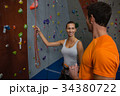 Friends discussing while standing by climbing wall 34380722