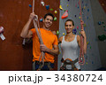 Portrait of athlete holding rope while standing by climbing wall at gym 34380724