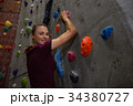Portrait of confident female athlete climbing wall in gym 34380727