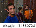 Portrait of confident man with climbing rope in gym 34380728