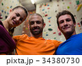 Portrait of confident male trainer with athletes in gym 34380730