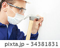Worker putting nail into wall 34381831