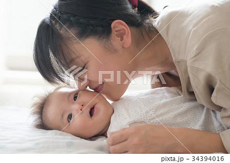 赤ちゃんの頬にキスする母親 34394016