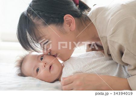 赤ちゃんの頬にキスする母親 34394019