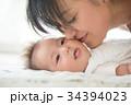 赤ちゃんの頬にキスするママ  34394023