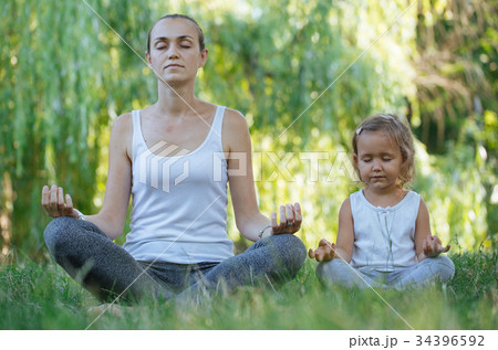 Young mother and cute little daughter meditating 34396592