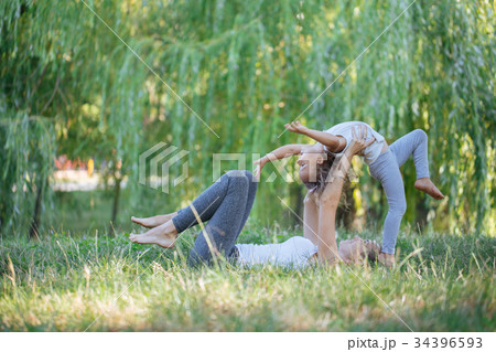 Mother and daughter doing yoga exercises on grass 34396593