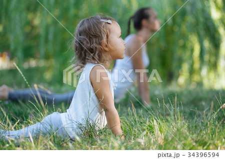 Mother and daughter doing yoga exercises on grass 34396594