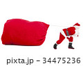 Santa claus carrying a heavy gift sack 34475236