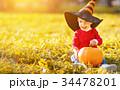 baby boy with pumpkin outdoors in halloween 34478201