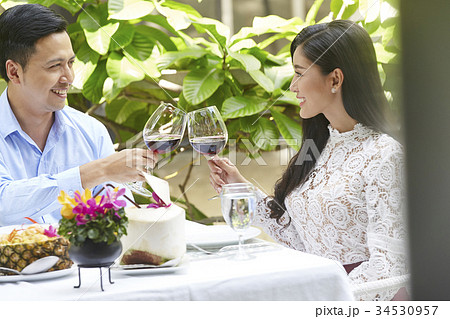 young happy couple on romantic lunch date drinking glass of red wine