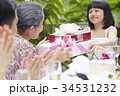 an adorable girl is giving gifts to her grandmother in her anniversary 34531232