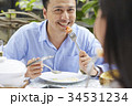 a handsome man is smiling and eating with his wife in a restaurant 34531234