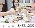 a young asian woman is having dinner and cheering up with family in a restaurant 34531235