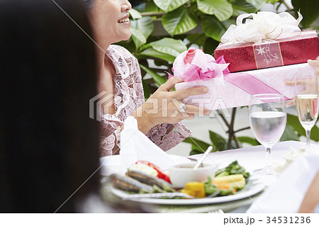 a woman is getting gifts from someone in her birthday party 34531236