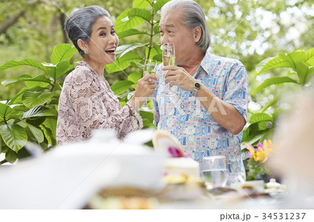 an old couple is having fun and enjoying wine together outdoors 34531237