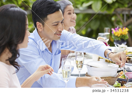 a luxurious man is smiling and sharing food for his wife at a party in a restaurant 34531238